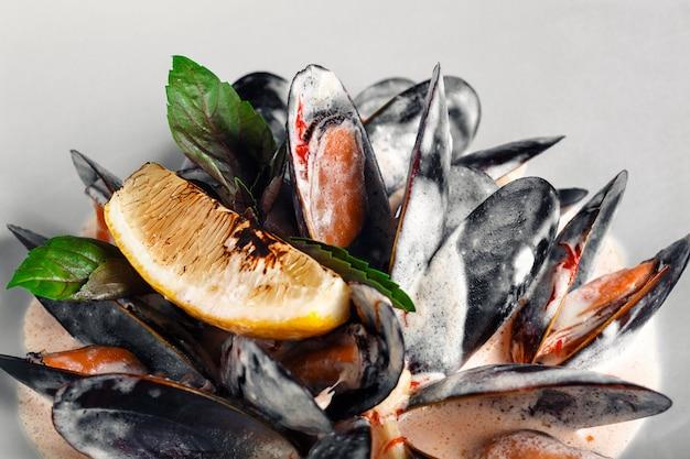 Moules de fruits de mer à la crème, citron et basilic dans une assiette blanche