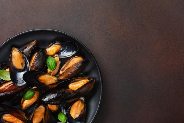 Moules de fruits de mer dans une assiette noire avec des feuilles de basilic sur fond rouillé