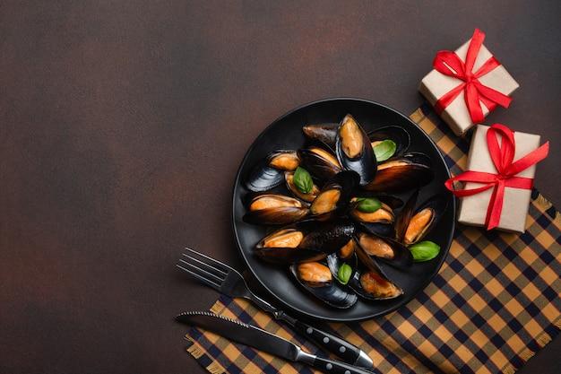 Moules de fruits de mer et feuilles de basilic dans une assiette noire avec des boîtes de fourchette, couteau et cadeau sur une serviette et fond rouillé