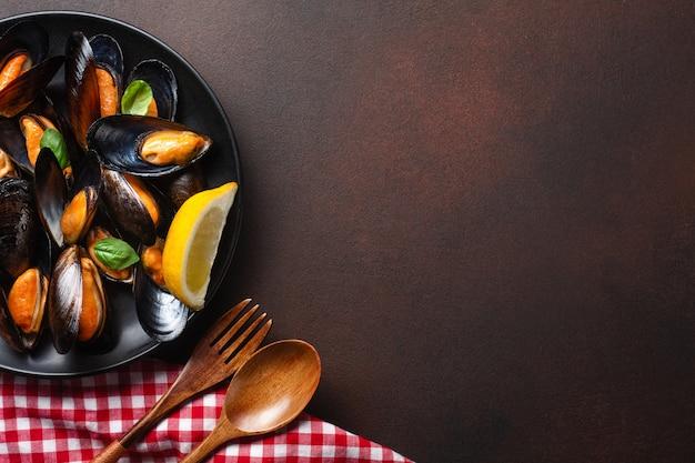 Moules de fruits de mer et feuilles de basilic dans une assiette noire avec une serviette, des tranches de pain, une cuillère et une fourchette en bois