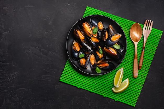 Moules de fruits de mer et feuilles de basilic dans une assiette noire sur une table en bambou et pierre