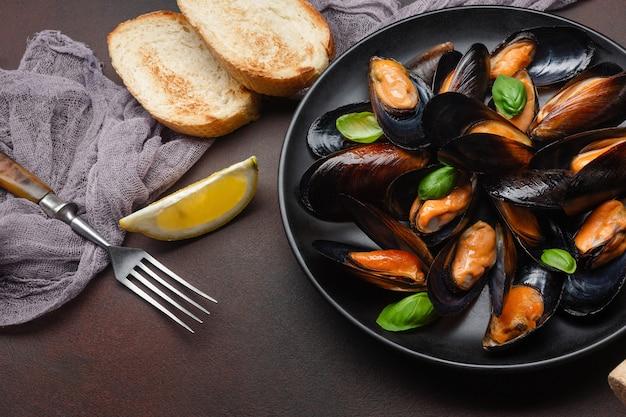 Moules de fruits de mer et feuilles de basilic dans une assiette noire avec tranche de pain, citron et fourchette