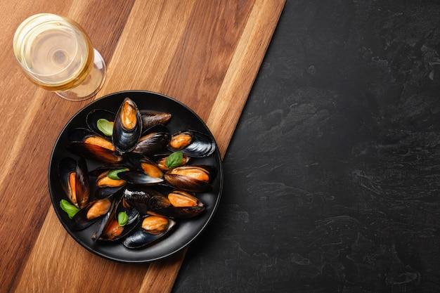 Moules de fruits de mer et feuilles de basilic dans une assiette noire avec verre à vin, citron, couteau sur planche de bois et table en pierre