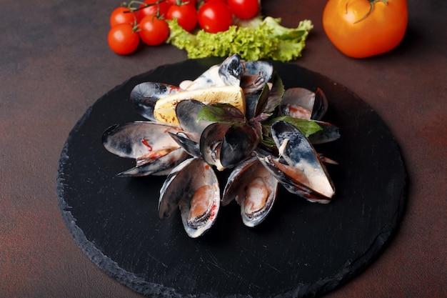 Moules de fruits de mer en sauce à la crème au citron et basilic sur un fond de pierre et rouillé