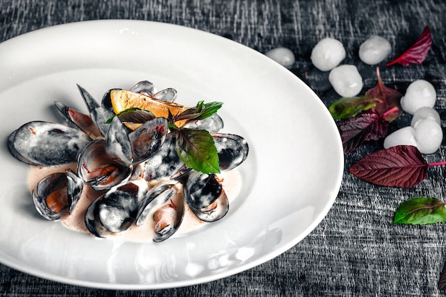 Moules de fruits de mer en sauce crème au citron et basilic sur un tableau noir