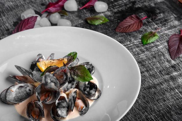 Moules de fruits de mer en sauce à la crème au citron et basilic sur un tableau noir