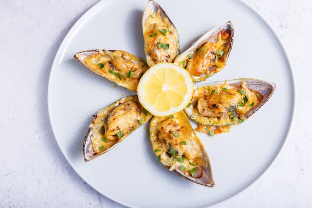 Moules greenshell cuites dans une demi-coquille avec du fromage, du persil et du citron sur une assiette blanche. apéritif chaud traditionnel. gros plan, vue de dessus.