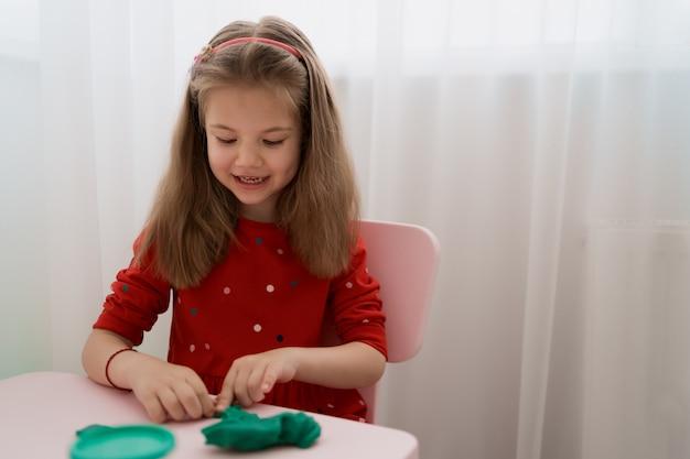 Moules de petite fille mignonne de pâte à modeler sur la table