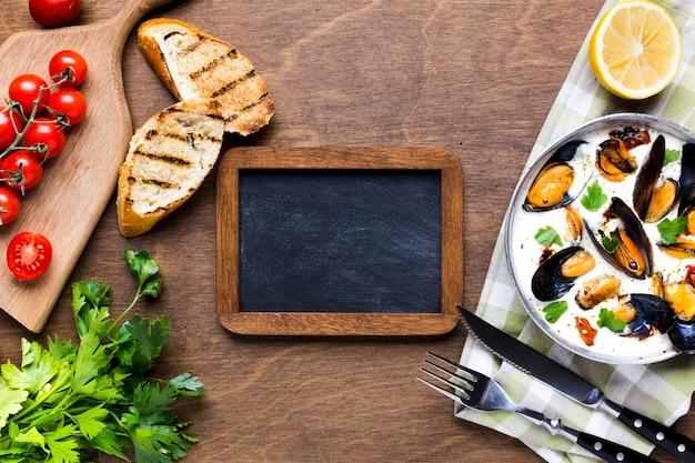Moules plates en sauce blanche sur nappe avec tableau noir