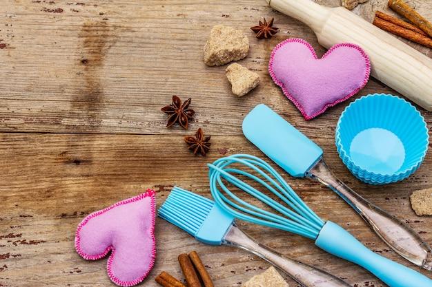 Moules en silicone pour cupcakes, épices, sucre, fouet, spatule, rouleau à pâtisserie et coeurs en feutre. planches en bois anciennes