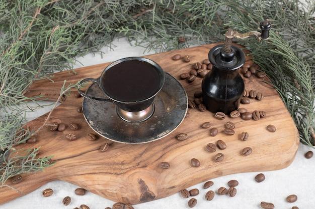 Moulin à café, haricots et arôme de café sur planche de bois
