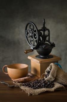 Moulin à café manuel vintage avec grains de café et tasse
