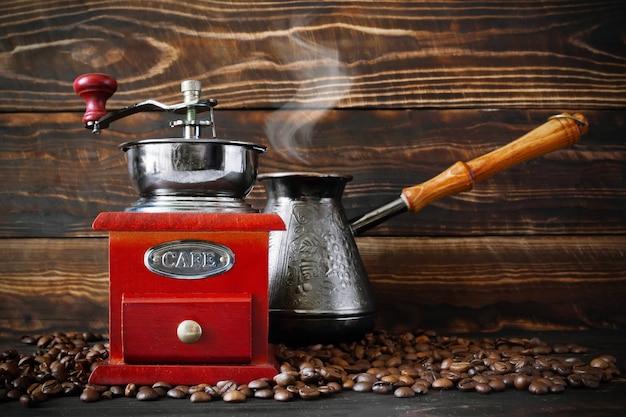 Moulin à café rétro en bois et cafetière en argent avec de la vapeur sur une surface sombre avec des grains autour.