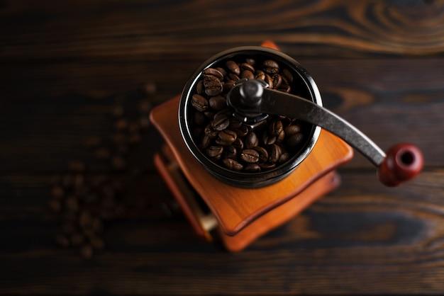Moulin à café sur une table en bois dans un style rustique. grains de café dans un moulin à café manuel sur une table rustique de couleur sombre.