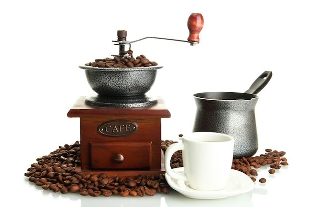 Moulin à café, turc et tasse de café avec des grains sur blanc