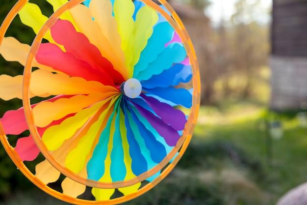 Moulin à vent coloré tournant dans le vent devant un fond vert naturel.focus sur le centre du moulinet.jouet coloré. liberté et concept drôle éolienne de jouet floue