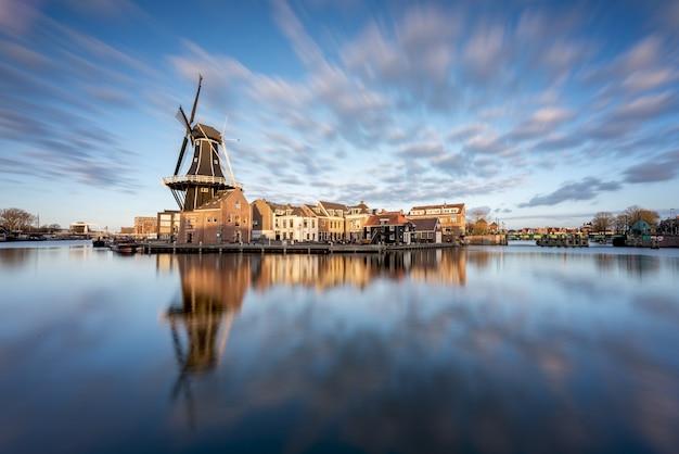 Moulin à vent et maisons traditionnelles, haarlem, hollande au coucher du soleil