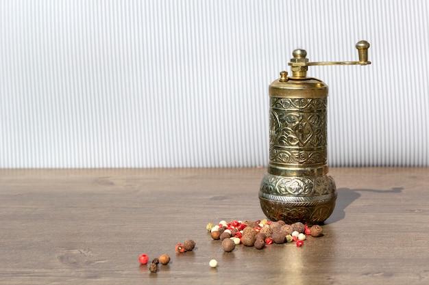 Moulin vintage pour le poivre avec les grains de poivre noirs et piment de la jamaïque sur table en bois. appareils de cuisine pour moudre les épices et le sel.