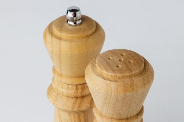 Moulins en bois avec sel et poivre sur fond blanc