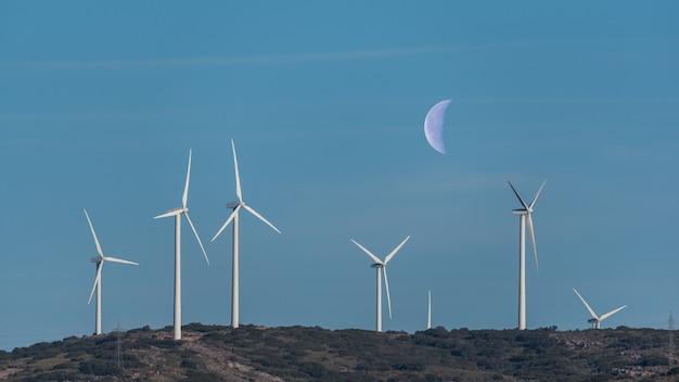 Moulins à vent sur une colline avec ciel et la lune