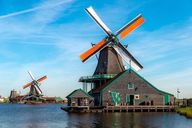 Moulins à vent hollandais traditionnels situés près de la rivière zaan, à zaanse schans, aux pays-bas.