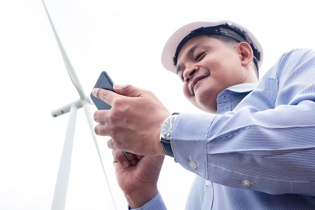 Les moulins à vent des ingénieurs travaillent sur smartphone avec l'éolienne derrière