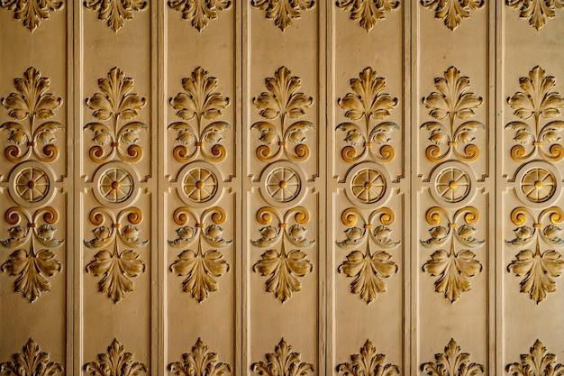 La moulure à motifs de feuilles au plafond est blanche et dorée