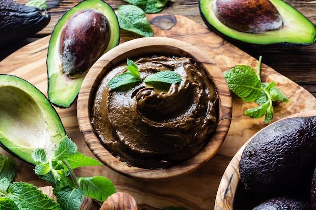 Mousse au chocolat à l'avocat dans un bol en bois d'olivier