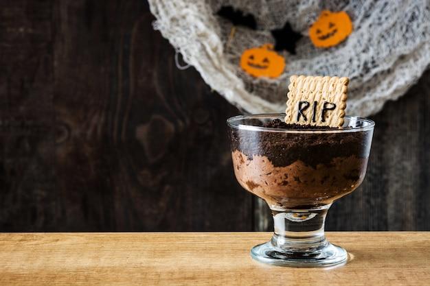 Mousse au chocolat halloween drôle avec cookie tombeau et araignées sur l'espace de copie de table en bois