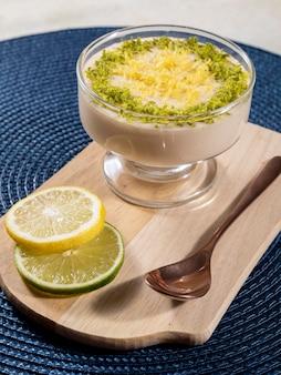 Mousse au citron dans un bol en cristal avec des zestes de citron.