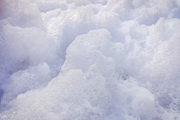 Mousse blanche d'un savon isolé à utiliser comme arrière-plan.