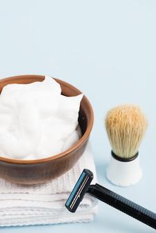 Mousse dans un bol en bois sur une serviette pliée blanche avec blaireau et rasoir sur fond bleu