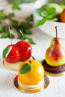 Mousse dessert en forme de poire, fruit orange et cerise