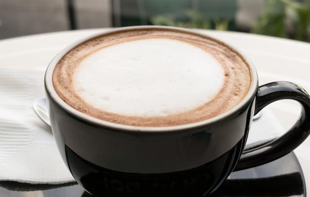 Mousse de lait en haut de la tasse à café.