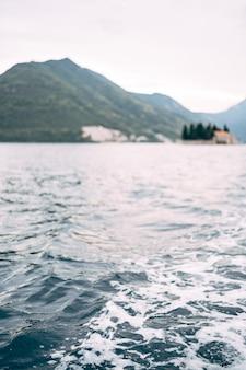 Mousse en mer une vague d'un bateau dans la baie de kotor dans le contexte des îles de perast
