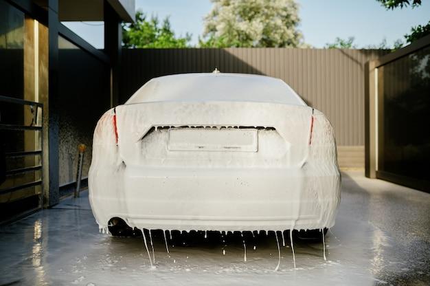 Mousse de nettoyage sur la voiture, station de lavage de voiture à la main, personne. industrie de lavage de voiture, lave-auto
