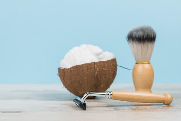 Mousse à raser dans un bol en noix de coco et accessoires de rasage en bois sur une table en bois.