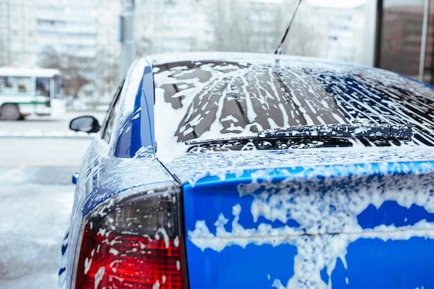 De la mousse de savon coule sur le verre. lave-auto en libre-service