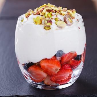 Mousse à la vanille avec fraises, bleuets et pistaches