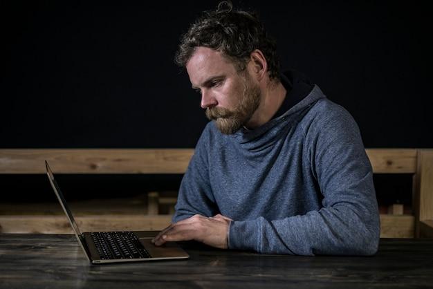 Moustache hipster avec une barbe travaille à l'ordinateur