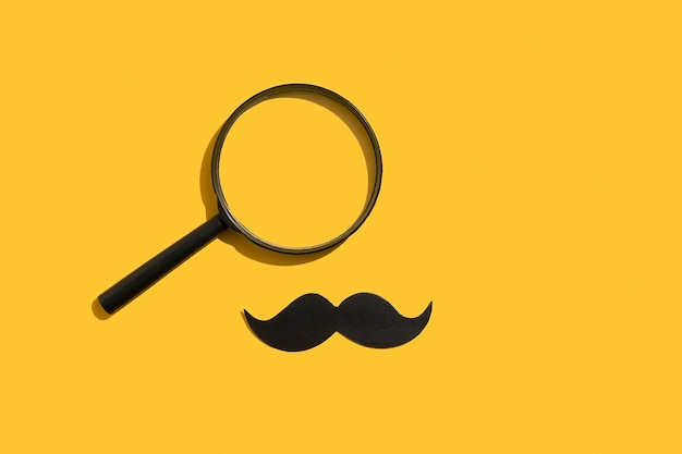 Moustache et loupe sur fond jaune