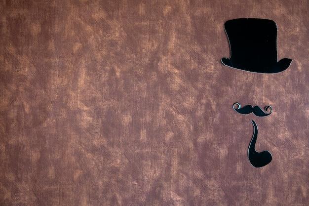Moustache noire et chapeau sur texture de fond en cuir marron avec espace de copie, concept de la journée internationale des hommes et de la fête des pères