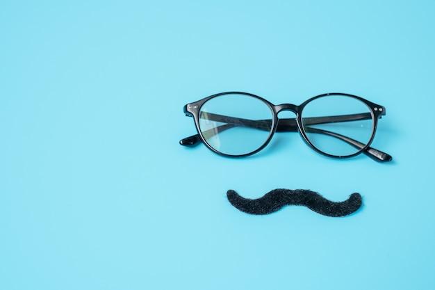 Moustache noire minimale et lunettes sur fond bleu. bonne fête des pères et concepts de la journée internationale des hommes