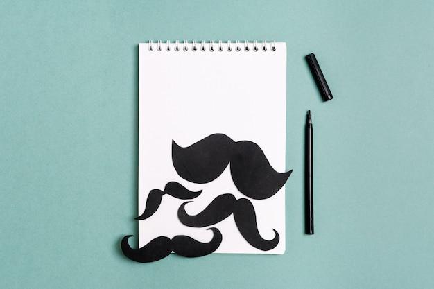 Moustache de papier noir, bloc-notes, crayon sur fond bleu mois dons de contrôle de la prosta