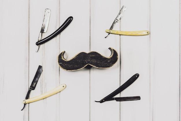 Moustache et rasoirs sur fond blanc