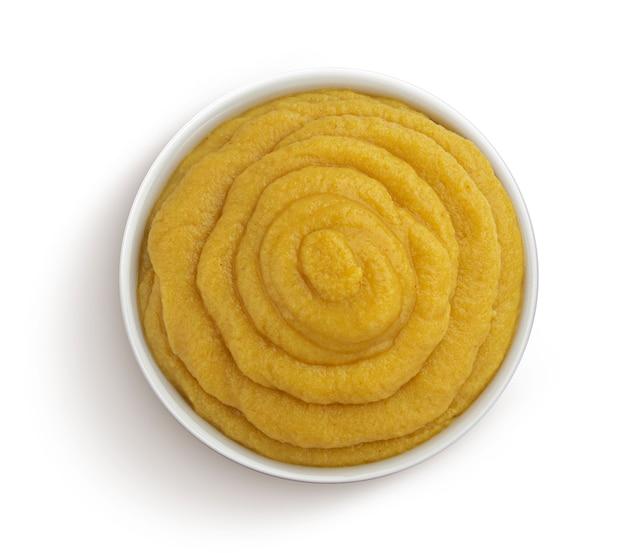 Moutarde dans un bol isolé sur tableau blanc avec un tracé de détourage, vue de dessus de la purée de légumes