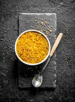 Moutarde de dijon dans le bol. sur noir rustique