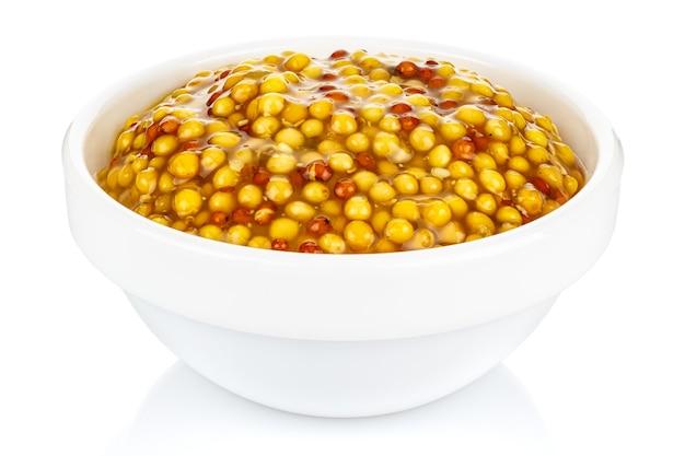 Moutarde française dans un petit bol rond en céramique blanche isolé sur fond blanc