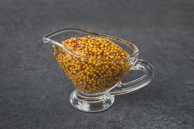 Moutarde française dans une saucière en verre sur une surface grise