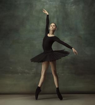Mouvement artistique. danse de ballerine classique gracieuse, posant isolé sur fond de studio sombre. tutu noir élégance. concept de grâce, de mouvement, d'action et de mouvement. semble en apesanteur, flexible. à la mode.